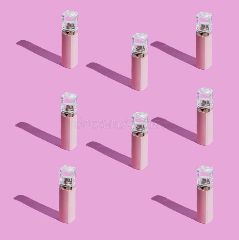 Muchas botellas de perfume Botellas de color rosado con un casquillo transparente fotografía de archivo libre de regalías