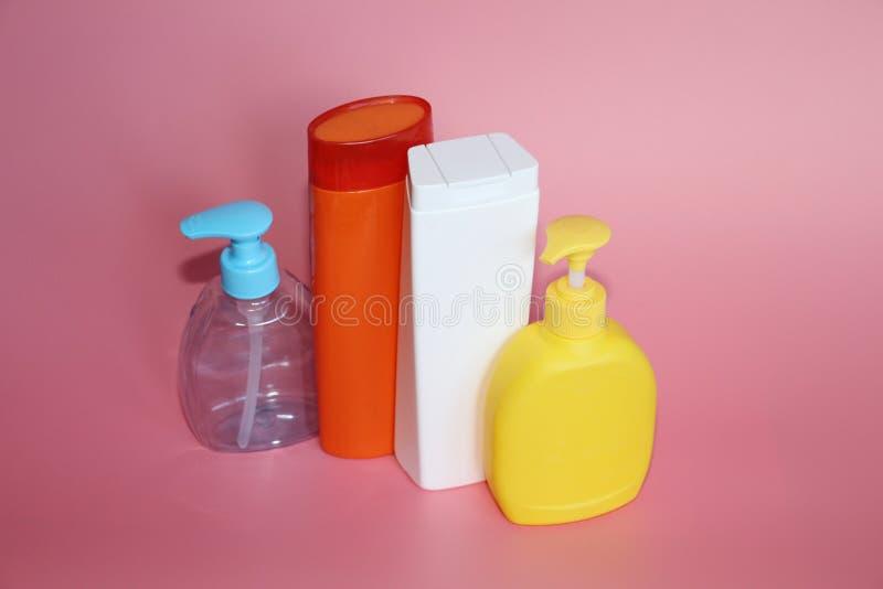 Muchas botellas plásticas en un fondo rosado Botellas para los cosméticos imagen de archivo
