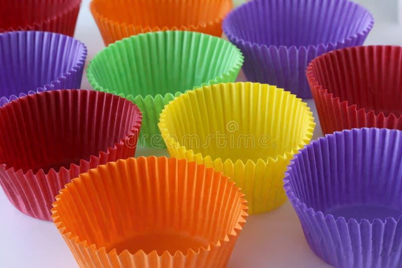 Muchas cápsulas de papel vacías coloridas de las formas para los molletes y las magdalenas en el fondo blanco - postre que cuece  fotos de archivo libres de regalías