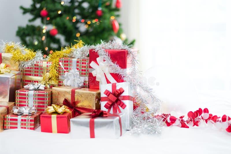 Muchas cajas de regalo de la Navidad con el ?rbol de navidad en la s?bana blanca D?a de fiesta y concepto de la celebraci?n Tema  foto de archivo