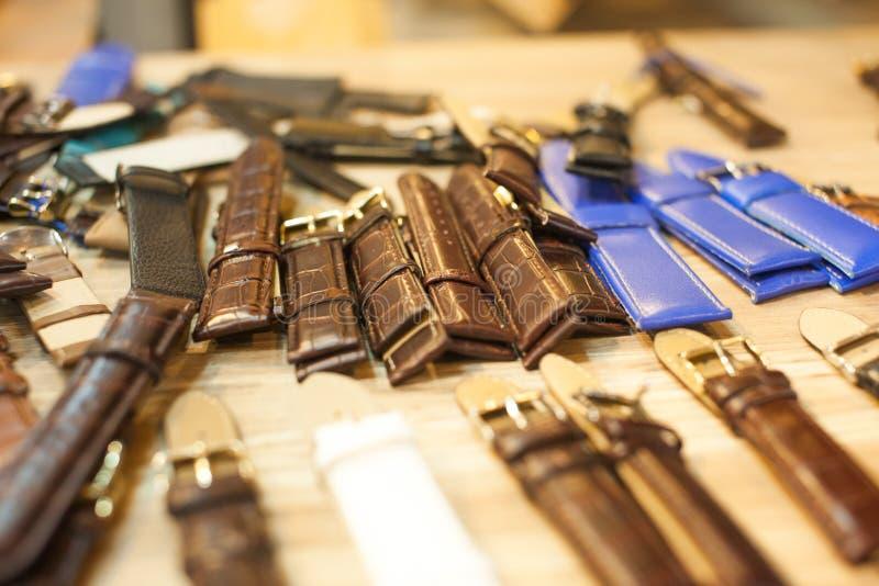 Muchas correas de reloj del vintage en la tabla de madera para la reparación fotos de archivo