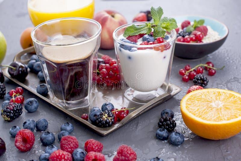 Muchas diversas frutas y bayas Vitaminas y comida sana Zumo de naranja en un vidrio, yogur, muesli con las bayas y fragante imagenes de archivo