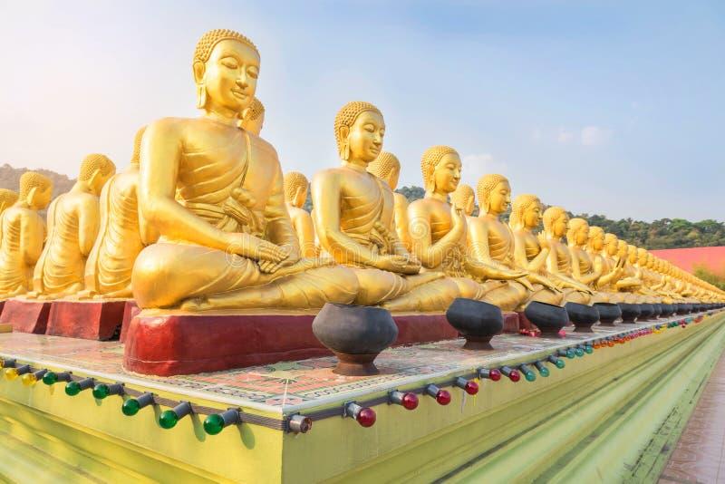 Muchas estatuas de oro de Buda que se sientan en fila en el nakornnayok público Tailandia del templo imagenes de archivo