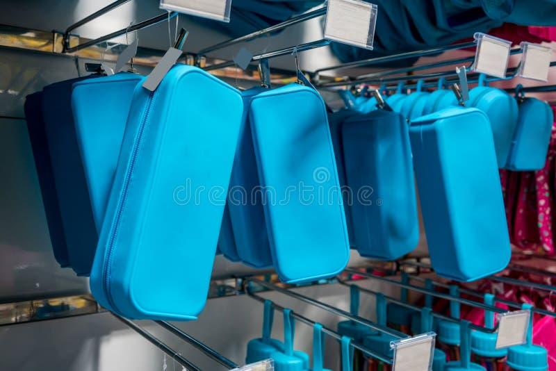 Muchas filas de corrigen las cajas que cuelgan en el estante del metal en tienda imagenes de archivo