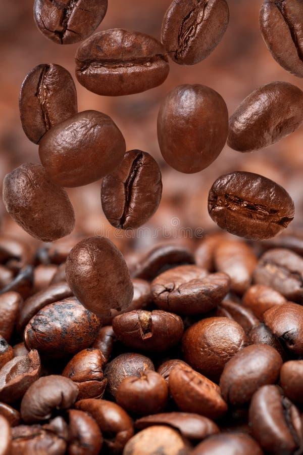 Muchas habas que caen y café asado oscuridad imagen de archivo