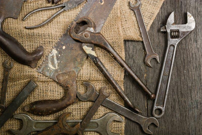 Muchas herramientas oxidadas viejas dispersaron en el tstolu de madera Visión desde arriba imagenes de archivo