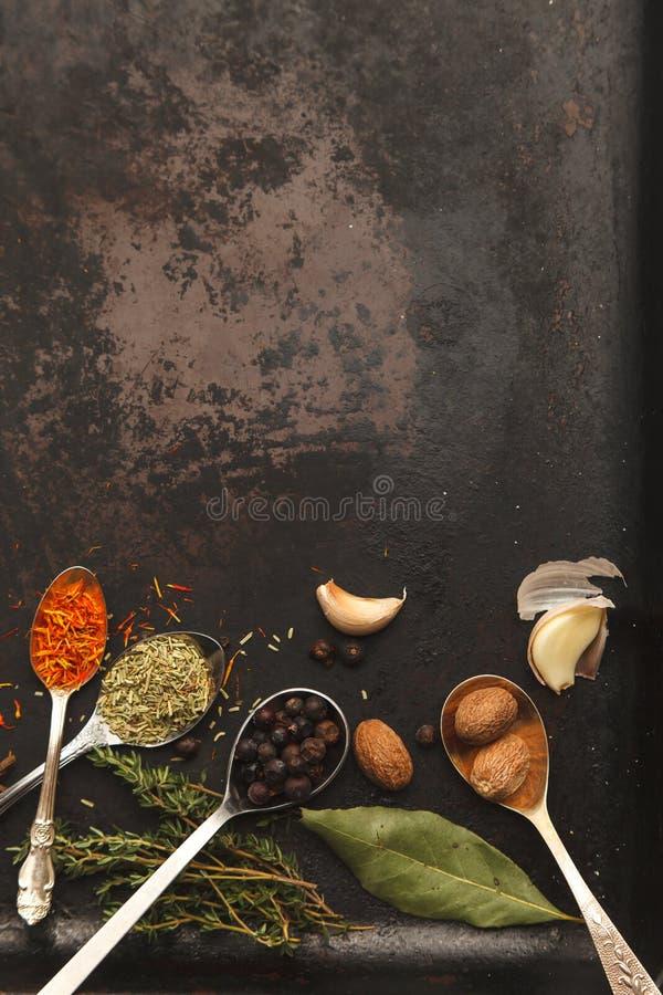 Muchas hierbas y especias en la tabla vieja negra imagen de archivo