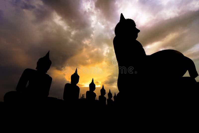 Muchas imágenes grandes de Buda y cielos anaranjados en el distrito de Thung Yai fotografía de archivo