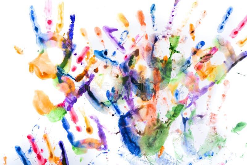 Muchas impresiones multicoloras de la mano en blanco foto de archivo