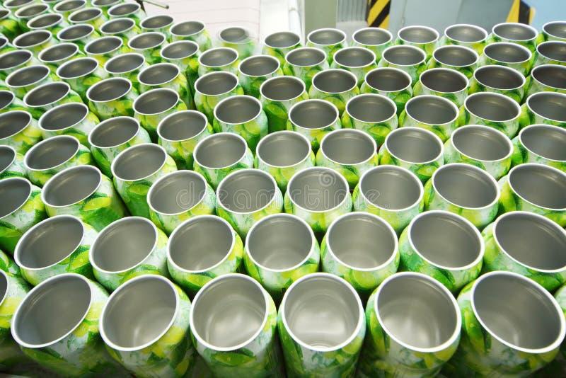 Muchas latas de aluminio abiertas para las bebidas se mueven en transportador imagen de archivo