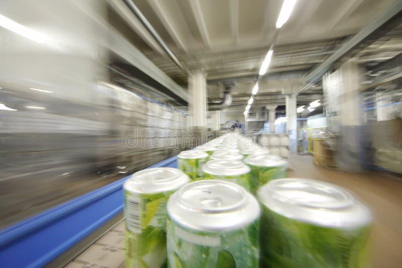 Muchas latas verdes con las bebidas van en transportador fotografía de archivo