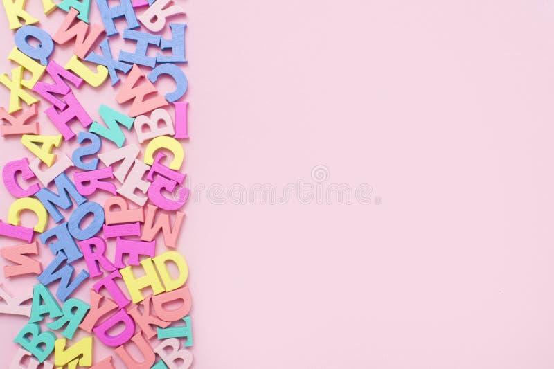 Muchas letras de madera multicoloras en un fondo rosado Letras del juguete Alfabeto ingl?s Visi?n desde arriba Endecha plana Copi fotografía de archivo libre de regalías