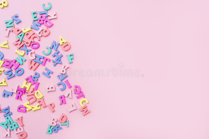 Muchas letras de madera multicoloras en un fondo rosado Letras del juguete Alfabeto ingl?s Visi?n desde arriba Endecha plana Copi imagen de archivo