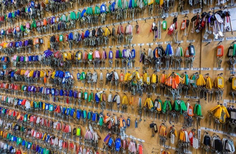 Muchas llaves con las etiquetas dominantes plásticas coloridas que cuelgan en los ganchos en el tablero de madera fotografía de archivo