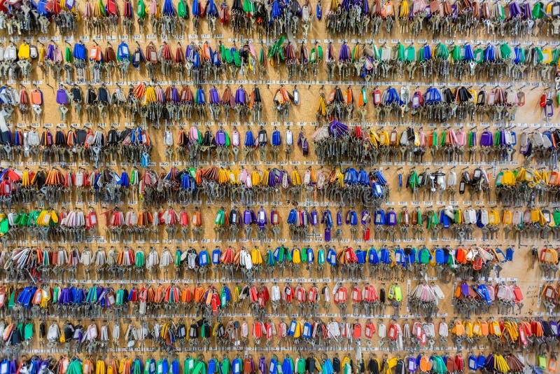 Muchas llaves con las etiquetas dominantes plásticas coloridas que cuelgan en los ganchos en el tablero de madera imagenes de archivo