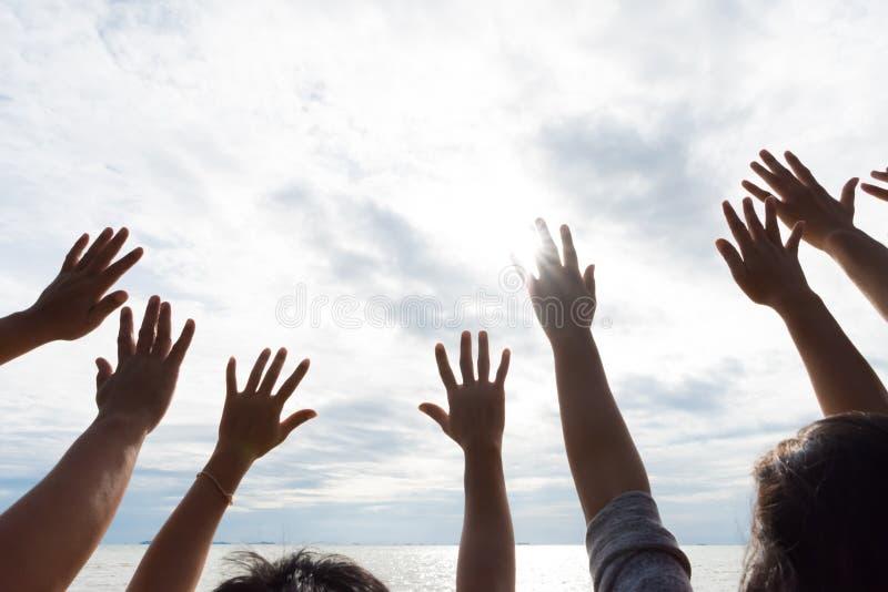 Muchas manos aumentaron para arriba contra el cielo azul Amistad, trabajo en equipo fotografía de archivo