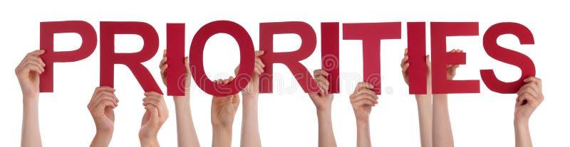 Muchas manos de la gente que llevan a cabo prioridades rectas rojas de la palabra imagen de archivo