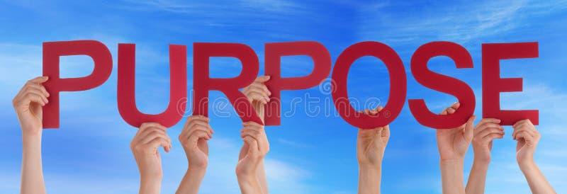 Muchas manos de la gente que sostienen el cielo azul del propósito recto rojo de la palabra imagenes de archivo