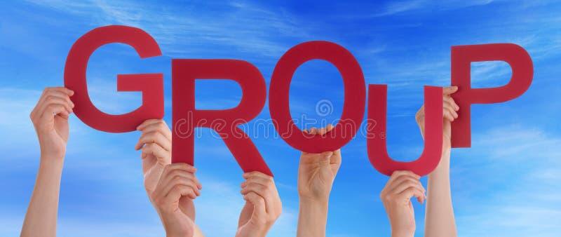 Muchas manos de la gente que sostienen el cielo azul rojo del grupo de palabra fotografía de archivo
