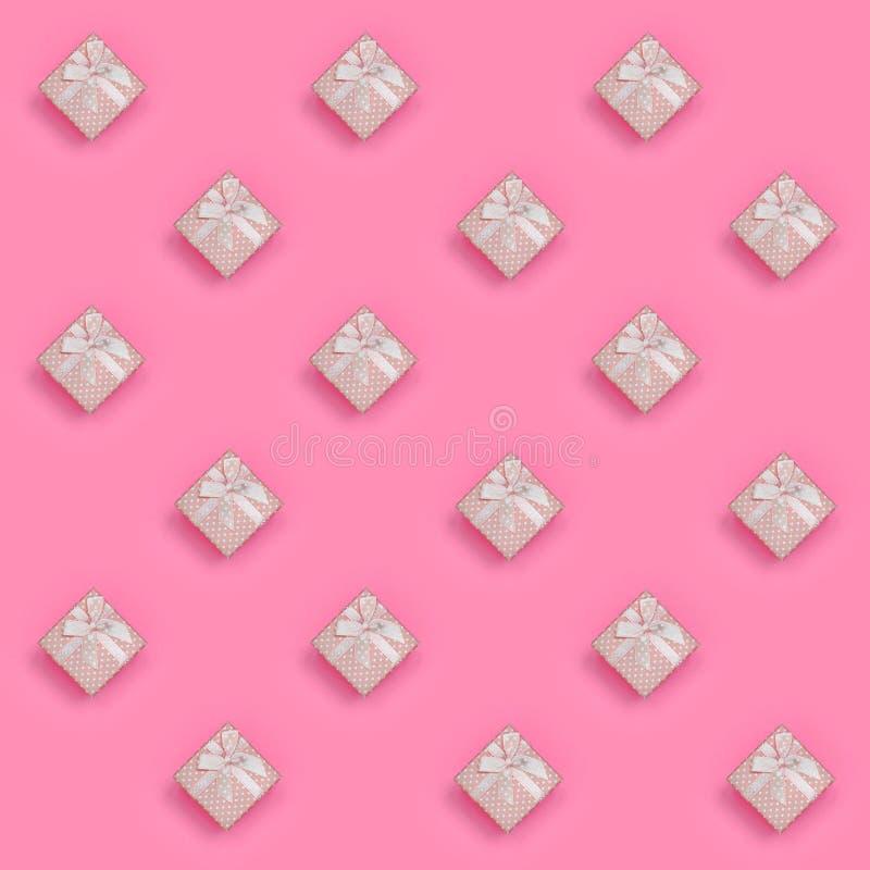 Muchas mentiras rosadas de las cajas de regalo en el fondo de la textura del papel rosado en colores pastel del color de la moda  libre illustration