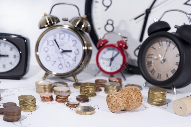 Muchas monedas con los relojes y el alcohol imagen de archivo libre de regalías