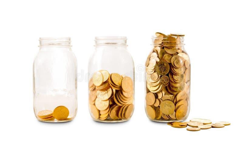 Muchas monedas de oro en tres botellas de cristal fotos de archivo