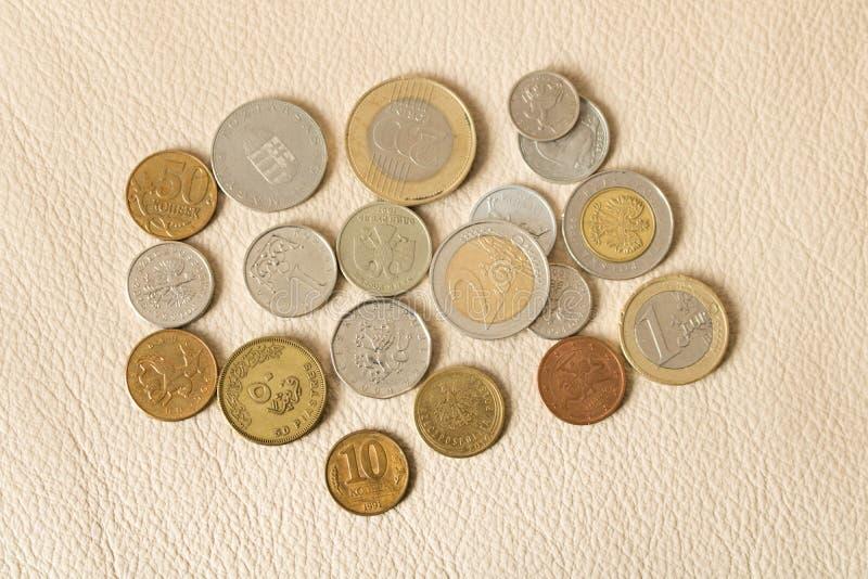 Muchas monedas dispersadas en un fondo de cuero imágenes de archivo libres de regalías