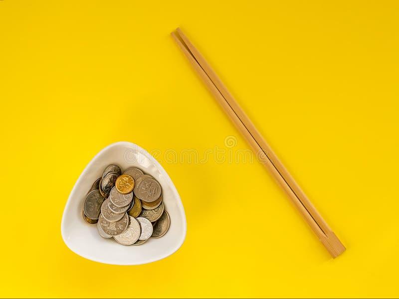 Muchas monedas en un cuenco blanco y palillos de madera en un fondo amarillo El concepto de la incapacidad para comer el dinero y fotografía de archivo