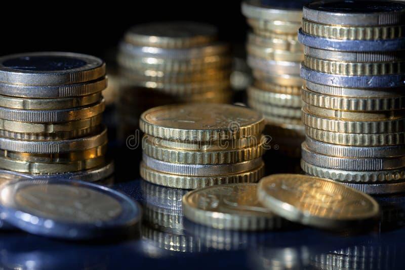 Muchas monedas y centavos euro en negro fotos de archivo