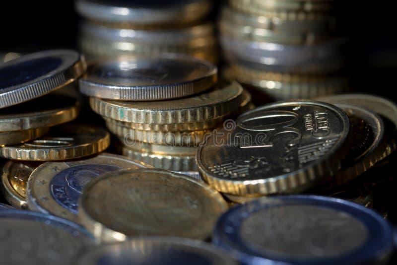 Muchas monedas y centavos euro en negro fotografía de archivo
