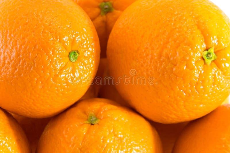 Muchas naranjas crudas frescas con los ombligos, fondo anaranjado imagenes de archivo
