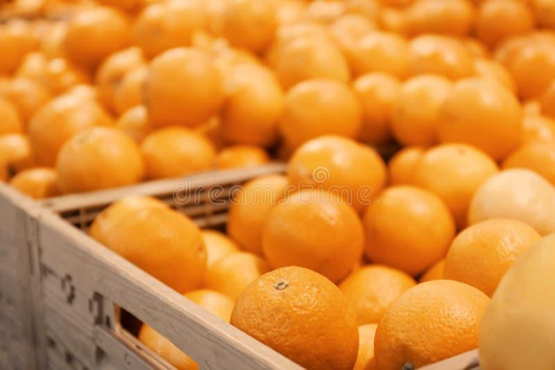 Muchas naranjas maduras en cajón plástico en contador del mercado Limones y cal fotos de archivo