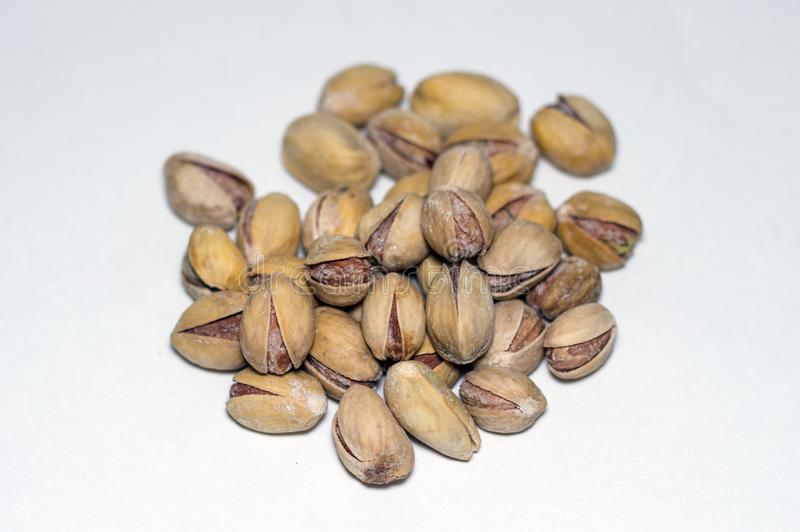 Muchas nueces de pistacho saladas se cierran encima de aislado en el fondo blanco imagenes de archivo