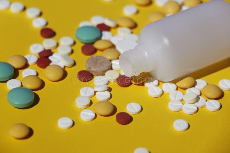 Muchas píldoras multicoloras en un fondo amarillo foto de archivo