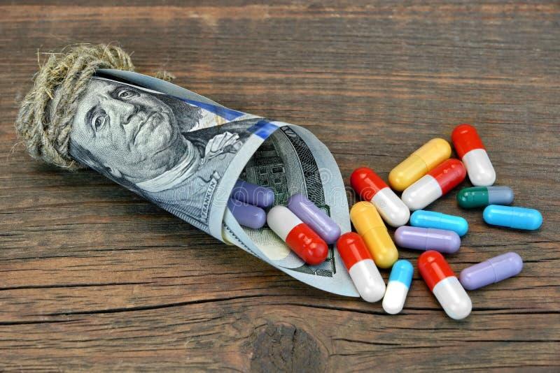 Muchas píldoras y cápsulas coloridas caídas del rollo del dinero imagen de archivo