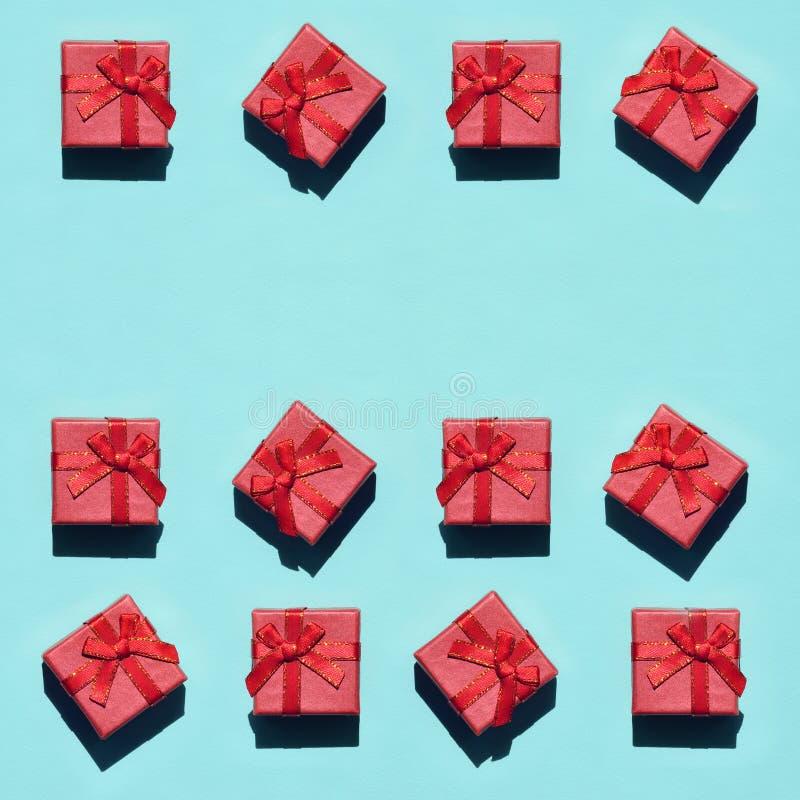 Muchas pequeñas cajas de regalo rosadas rojas en el fondo de la textura del papel azul en colores pastel de moda del color de la  fotografía de archivo