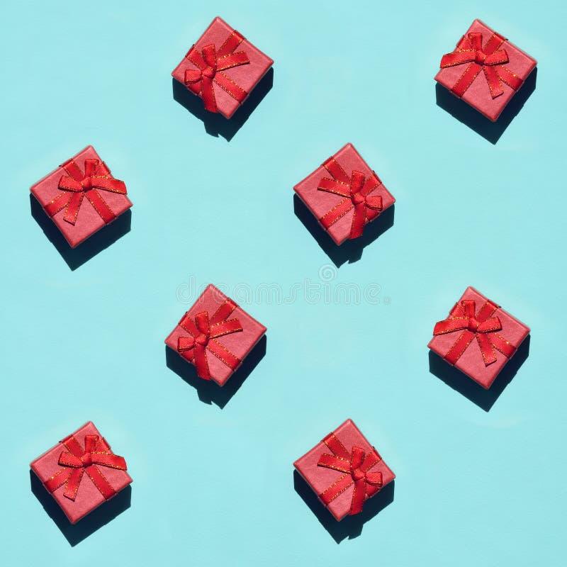 Muchas pequeñas cajas de regalo rosadas rojas en el fondo de la textura del papel azul en colores pastel de moda del color de la  fotos de archivo libres de regalías