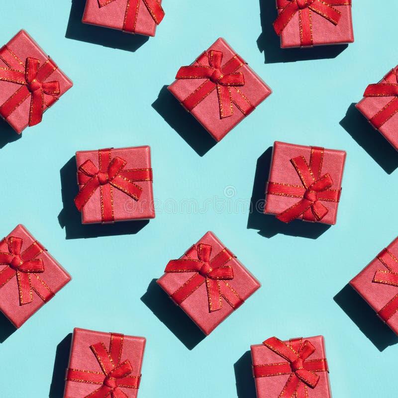 Muchas pequeñas cajas de regalo rosadas rojas en el fondo de la textura del papel azul en colores pastel de moda del color de la  fotografía de archivo libre de regalías