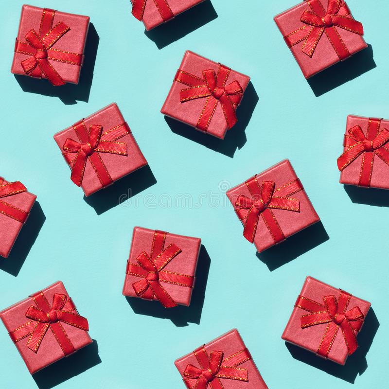 Muchas pequeñas cajas de regalo rosadas rojas en el fondo de la textura del papel azul en colores pastel de moda del color de la  foto de archivo libre de regalías