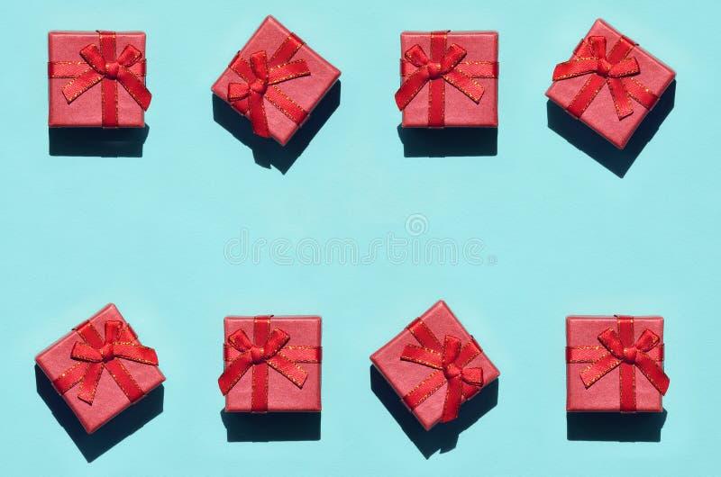 Muchas pequeñas cajas de regalo rosadas rojas en el fondo de la textura del papel azul en colores pastel de moda del color de la  fotos de archivo