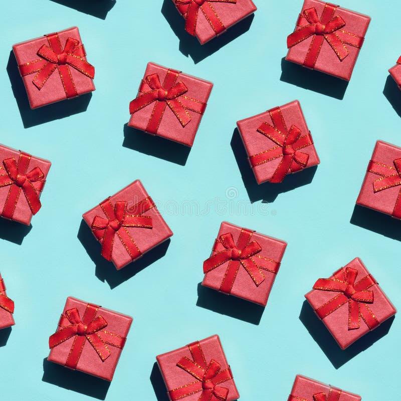 Muchas pequeñas cajas de regalo rosadas rojas en el fondo de la textura del papel azul en colores pastel de moda del color de la  imagenes de archivo