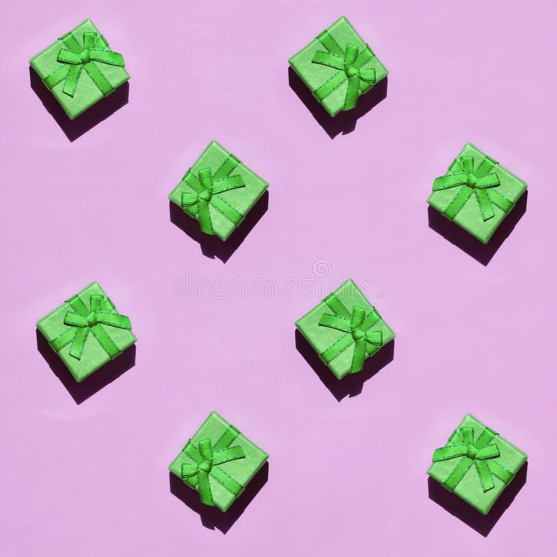 Muchas pequeñas cajas de regalo verdes en el fondo de la textura del papel rosado en colores pastel de moda del color de la moda foto de archivo