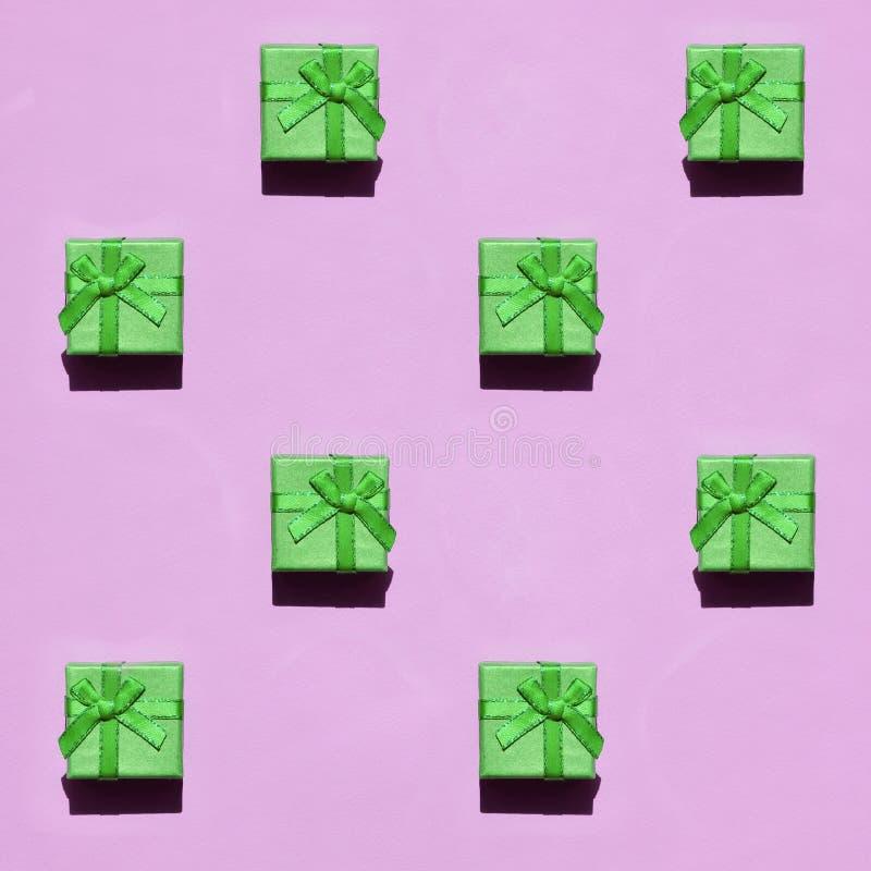 Muchas pequeñas cajas de regalo verdes en el fondo de la textura del papel rosado en colores pastel de moda del color de la moda imagen de archivo libre de regalías