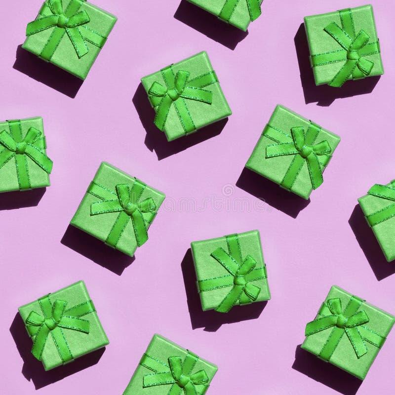 Muchas pequeñas cajas de regalo verdes en el fondo de la textura del papel rosado en colores pastel de moda del color de la moda imágenes de archivo libres de regalías