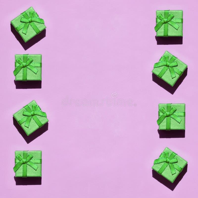 Muchas pequeñas cajas de regalo verdes en el fondo de la textura del papel rosado en colores pastel de moda del color de la moda imagen de archivo