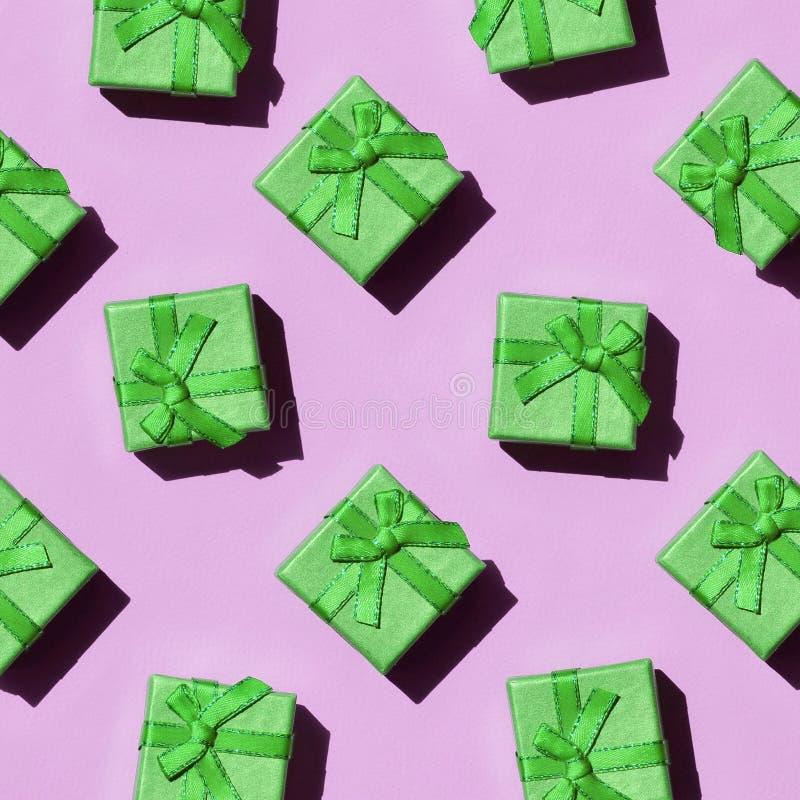 Muchas pequeñas cajas de regalo verdes en el fondo de la textura del papel rosado en colores pastel de moda del color de la moda fotos de archivo libres de regalías