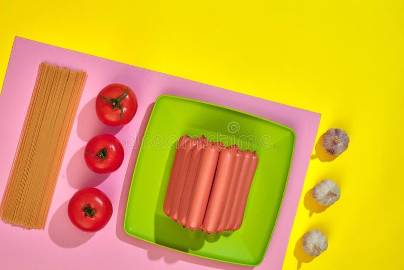 Muchas salchichas crudas en la placa En fondo amarillo con las pastas y las verduras, visión superior imagen de archivo libre de regalías