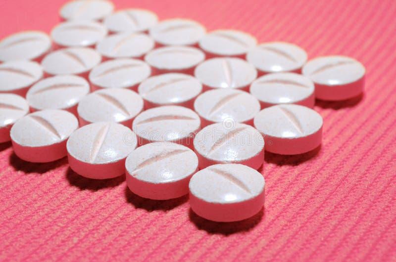 Muchas tabletas convexas lisas blancas con una tira de división en un fondo rayado rosado, en la forma de un rectángulo fotografía de archivo