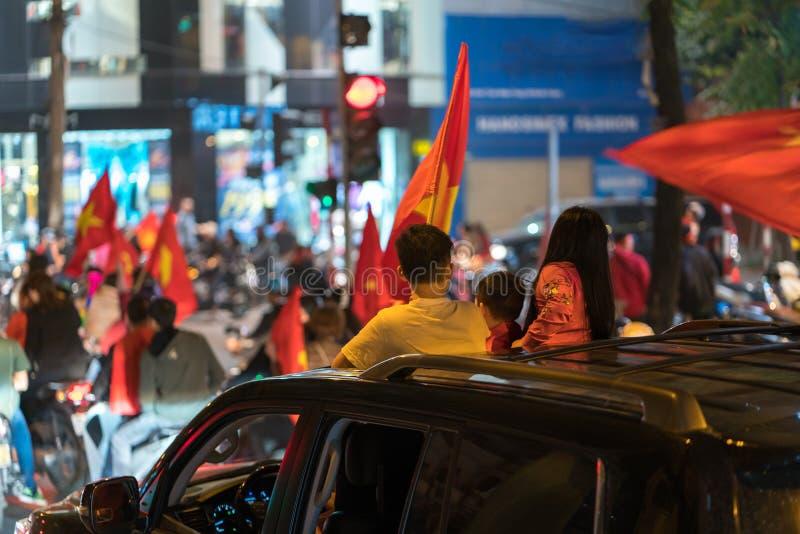 Muchedumbre de fanáticos del fútbol vietnamitas abajo de la calle para celebrar el triunfo después de fútbol, con muchas banderas fotos de archivo