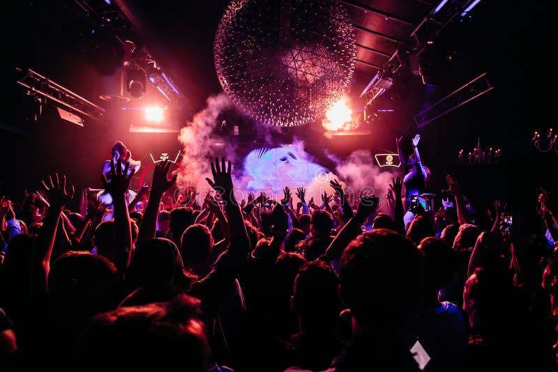 Muchedumbre de gente que baila en el club de noche fotos de archivo